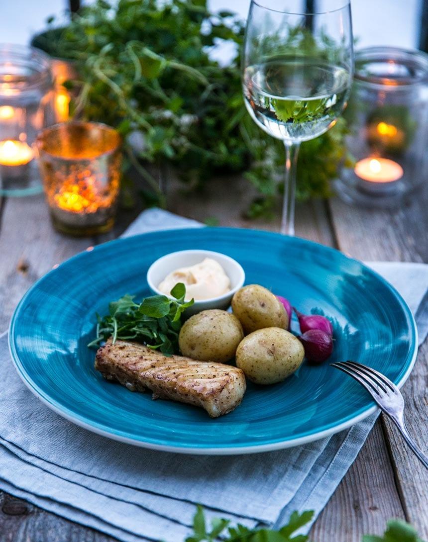 Torskrygg med smörslungad potatis, gröna blad, snabbpicklade rödlökar och lime-hollandaise