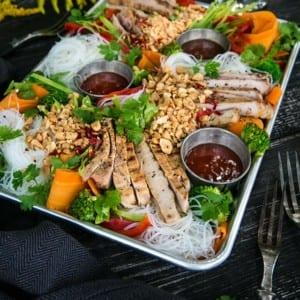 Panngrillade fläskkotletter med nudlar, grönsaker och jordnötter
